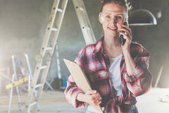 Young smiling businesswoman builder, engineer, architect, designer dressed in plaid shirt and construction glasses. Is standing, talking on cell phone and Royalty Free Stock Photos