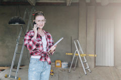 Young smiling businesswoman builder,engineer, architect,designer in workshop, talking on cell phone. Young smiling businesswoman builder,engineer, architect Royalty Free Stock Photos