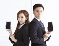 smiling businesswoman and businessman showing smart phone royalty free stock photo