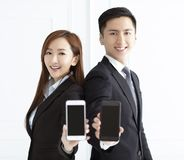 smiling businesswoman and businessman showing smart phone stock photos