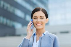 Young smiling businesswoman calling on smartphone Royalty Free Stock Image