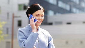 Young smiling businesswoman calling on smartphone stock video