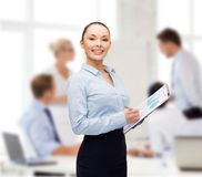 Young smiling businesswoman with clipboard and pen Royalty Free Stock Photo