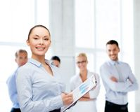 Young smiling businesswoman with clipboard and pen Stock Image