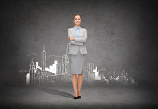 Young smiling businesswoman with crossed arms. Business and education concept - friendly young smiling businesswoman with crossed arms with city on the back stock image