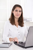 Young smiling businesswoman at desk in a bank royalty free stock image