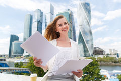 Young smiling businesswoman with heap of papers. Business, paperwork and people concept - young smiling businesswoman with heap of papers sitting on city bench Royalty Free Stock Photo