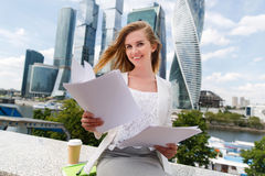 Young smiling businesswoman with heap of papers. Business, paperwork and people concept - young smiling businesswoman with heap of papers sitting on city bench Royalty Free Stock Photography