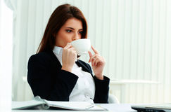 Young smiling businesswoman holding cup and drinking coffee Stock Photos