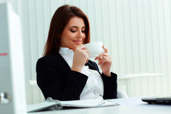 Young smiling businesswoman holding cup Royalty Free Stock Photos