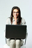 Young smiling businesswoman with laptop sitting on chair Stock Photo
