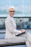 Young smiling businesswoman with notepad outdoors Stock Photo