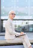 Young smiling businesswoman with notepad outdoors Stock Photography