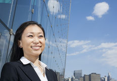 Young smiling businesswoman outside in front of glass building Stock Photography