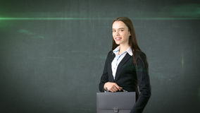 Young smiling businesswoman portrait with gray briefcase, dark background Royalty Free Stock Photography