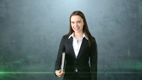 Young smiling businesswoman portrait with gray briefcase, dark background Stock Photography