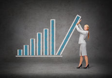 Young smiling businesswoman pushing up chart bar Royalty Free Stock Photo
