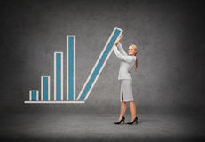 Young smiling businesswoman pushing up chart bar Stock Image