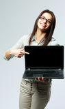 Young smiling businesswoman showing on a laptop screen Royalty Free Stock Images