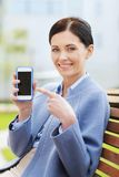 Young smiling businesswoman showing smartphone Stock Photo