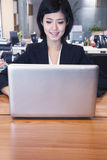 Young smiling businesswoman sitting in front of laptop, portrait Royalty Free Stock Image