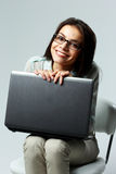 Young smiling businesswoman sitting with laptop Royalty Free Stock Image