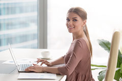 Young smiling businesswoman sitting at office desk looking at ca royalty free stock photo