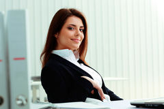 Young smiling businesswoman sitting at the table Royalty Free Stock Photos
