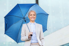 Young smiling businesswoman with umbrella outdoors Stock Image