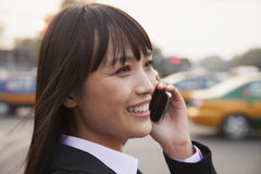 Young smiling businesswoman using the phone outside on the street in Beijing, close up portrait Stock Photos