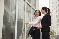 Young smiling businesswomen walking outside of the office, pointing in Stock Photos