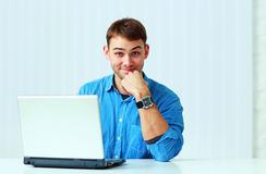Young smiling casual businessman in blue shirt sitting at the table Royalty Free Stock Photos