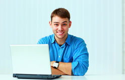 Young smiling casual businessman in blue shirt sitting at the table Royalty Free Stock Photography
