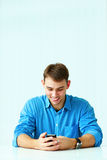 Young smiling casual businessman sitting at the table and looking at smartphone Stock Photography