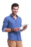Young smiling casual man holding a pad tablet Stock Image
