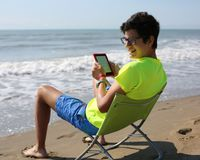 Smiling caucasian boy reads an ebook sitting on the beach chair Royalty Free Stock Photos