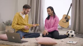 Young smiling Caucasian boy singing serenade and playing ukulele for his African American girlfriend. Couple in love stock video