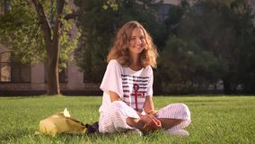 Young smiling caucasian brunette sitting in park on grass, looking in camera, laughing, university in the background
