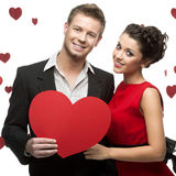 Young smiling caucasian couple holding red heart Stock Photography