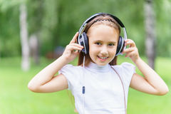 Young smiling caucasian girl listening music with professional DJ headphones and getting fun stock photo