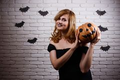Young smiling cheerful woman pumpkin in hands posing at camera. Halloween, celebration, party concept stock photos