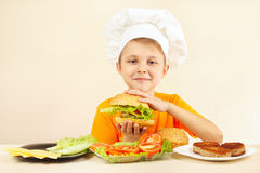 Young smiling chef in chefs hat enjoys cooking tasty hamburger Royalty Free Stock Images