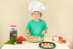 Young smiling chef in chefs hat enjoys cooking tasty pizza Royalty Free Stock Photo