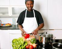 A young smiling chef cooking in the kitchen. A young smiling, happy chef cooking in the kitchen with passion Stock Photo