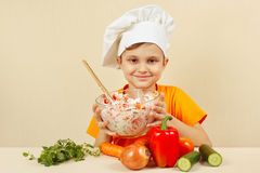 Young smiling chef prepared salad of fresh vegetables Stock Photo