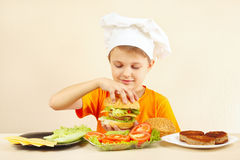 Young smiling chef shows how to cook hamburger Stock Image