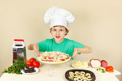 Young smiling chef shows how to cook pizza Stock Photography