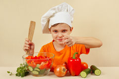 Young smiling chef shows how to cook vegetable salad Royalty Free Stock Photos