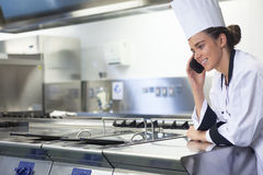 Young smiling chef standing next to work surface phoning Stock Photos