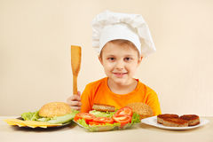 Young smiling chef at the table with ingredients is going to cook hamburger Royalty Free Stock Photography